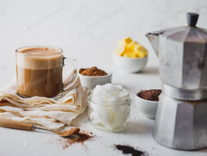 Cup of bulletproof coffe with cacao and ingredients on white background.