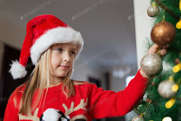 Cute Caucasian Little Girl decorating Christmas Tree at Home