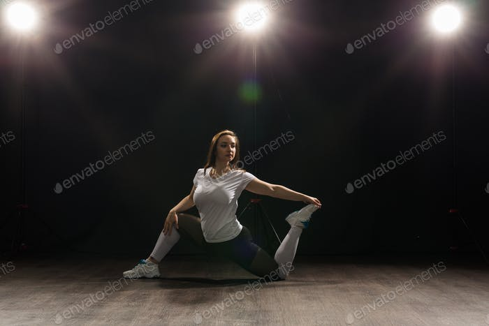 Young woman dancer gymnastics exercise pose on dark background