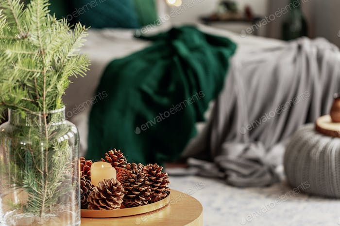 Spruce candle and cone on small wooden table in grey and emerald