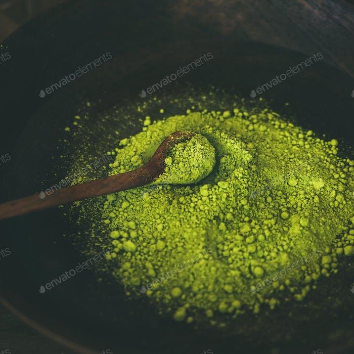 Japanese Matcha green tea powder in dark wooden bowl