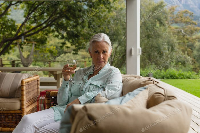 Portrait of active senior Caucasian woman having champagne in the porch at home