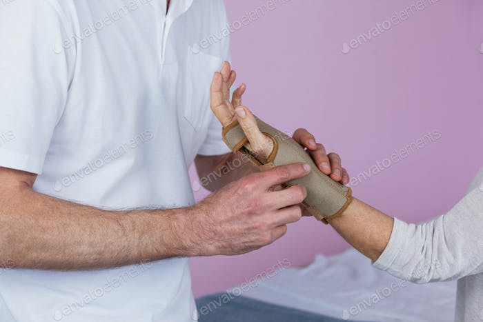 Mid section of physiotherapist examining a senior womans wrist