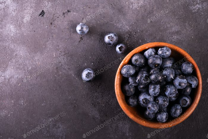 Freshly picked blueberries in wooden bowl on rustic table. Bilberry on stone background. Blueberry