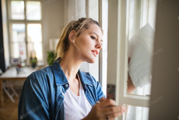 Young woman indoors at home, cleaning window.