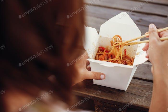 Wok mit Nudeln und Gemüse in Karton to go und Bambus Essstäbchen