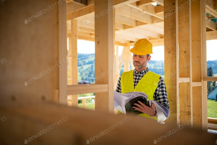 Engineer with hardhat and blueprints on building site of wood frame house under construction