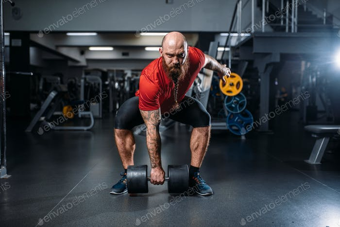 Male lifter doing exercise with dumbbells in gym
