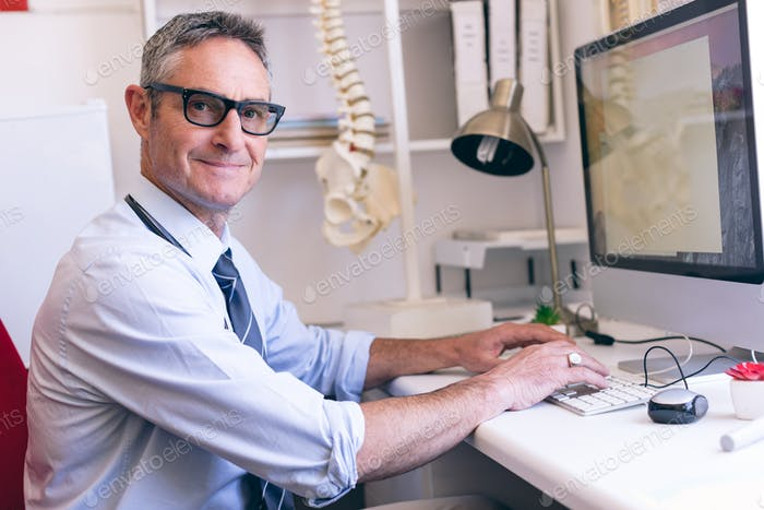 Portrait of confident Caucasian male doctor working on computer at clinic of retirement home
