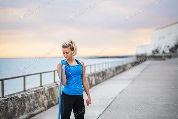 Young sporty woman runner with elastic bands outside on a beach, exercising.