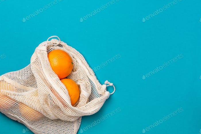 Ecological Reusable Shopping Bag with Fresh Orange Fruits on Vibrant Background