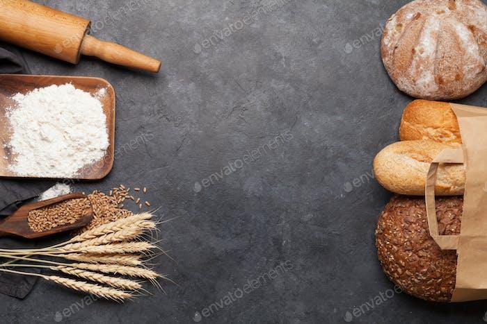 Diverse Brot mit Weizen, Mehl und Kochutensilien