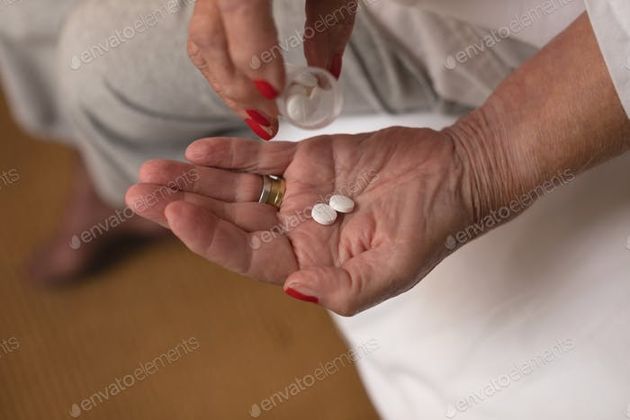 Mid section of senior woman taking pills in her hand on her bed at home