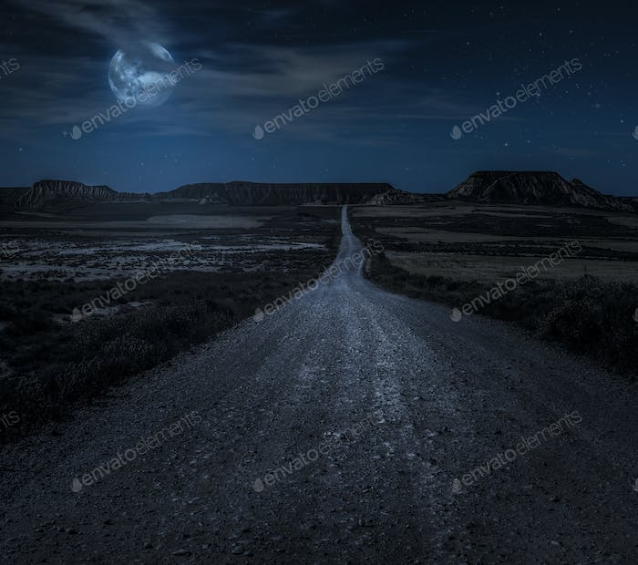 Moon, stars and clouds in the night. Wild west road illuminated