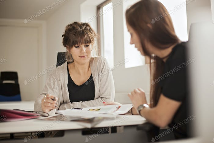 Businesswomen discussing about magazine during meeting in creative office