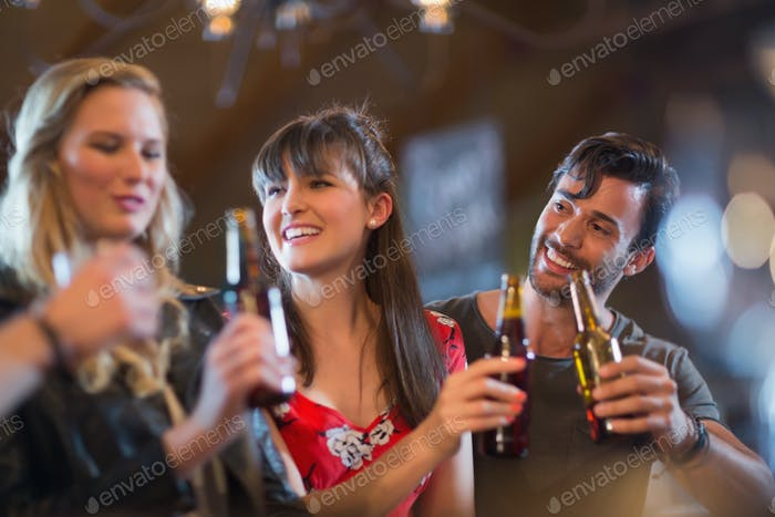 Smiling friends holding beer bottles