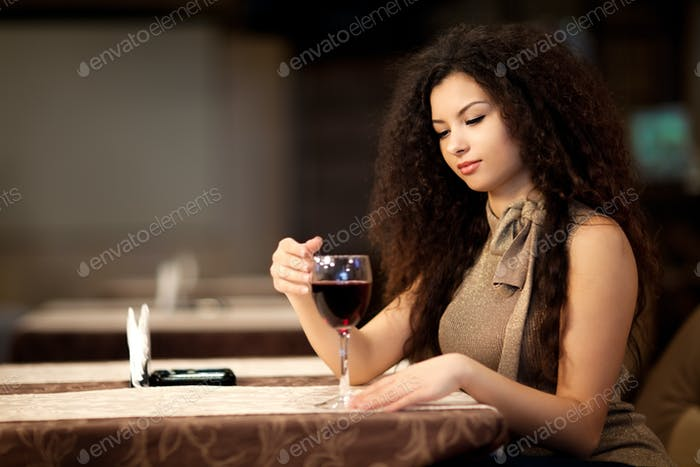 Girl with curly hair holding glass wine in hand