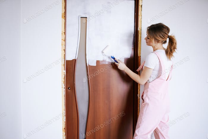 A girl in a pink work suit repaints an old door. Renovation and new life