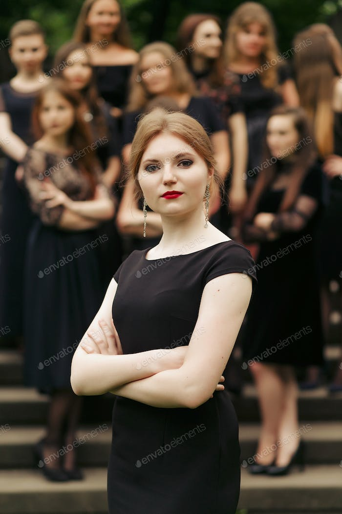 luxury gorgeous woman in black dress posing, standing in front of group of ladys