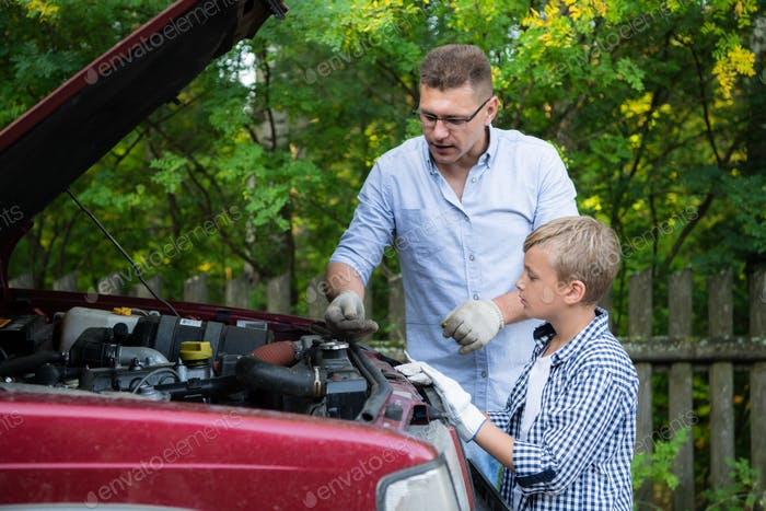 Dad and his son repairing car with open hood outdoors, fixing engine
