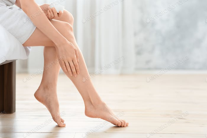 Cropped of unrecognizable lady applying body lotion