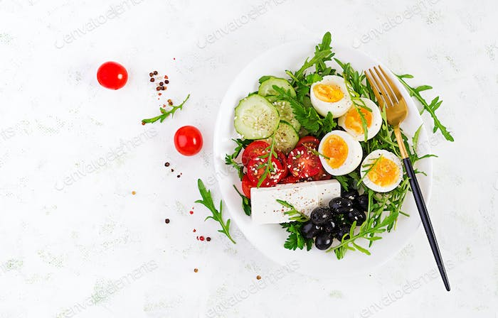Fresh vegetable salad with tomato,  cucumbers, olives, arugula and feta cheese