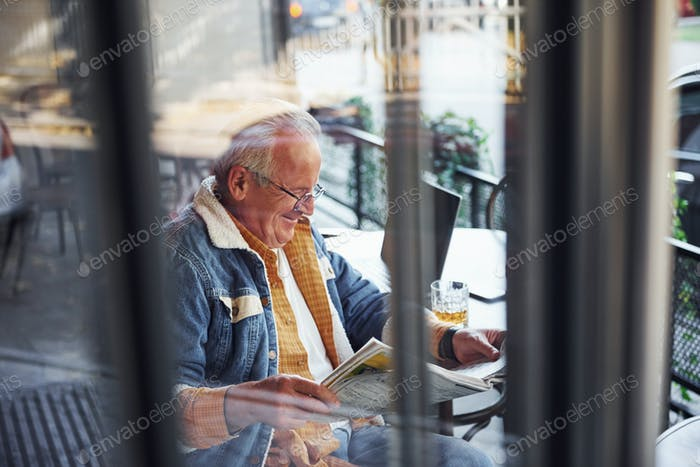 Stylish senior in fashionable clothes and in glasses sits in the cafe and reads newspaper