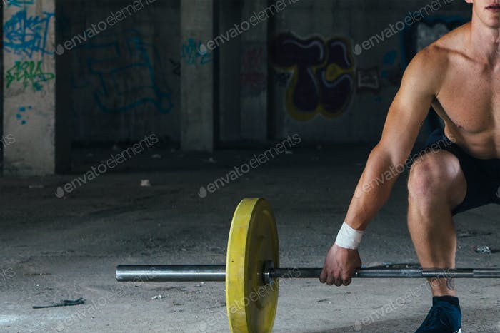 Faceless man lifting barbell