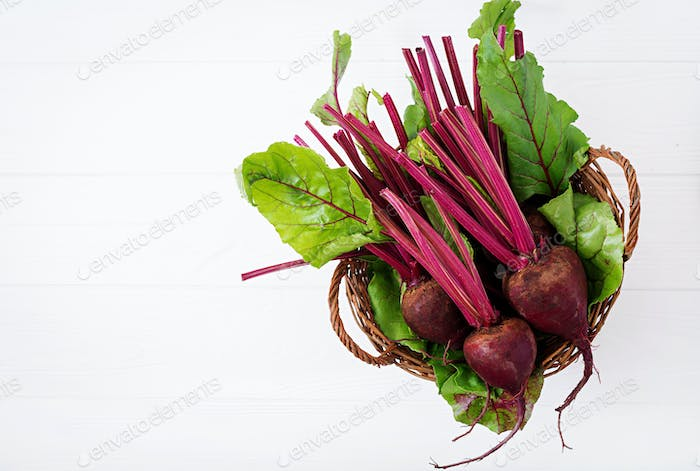 Young beetroot with a tops in basket on a white background. Flat lay. Top view