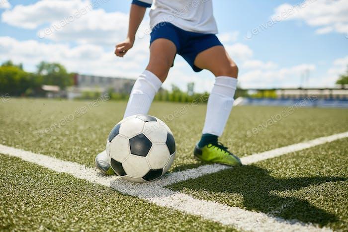 Teenage Boy Kicking Ball on Football Field