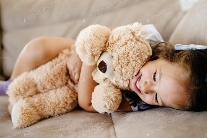 Cute little girl playing with teddy bear