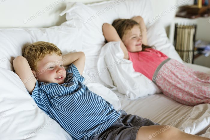 Little kids lying on the bed
