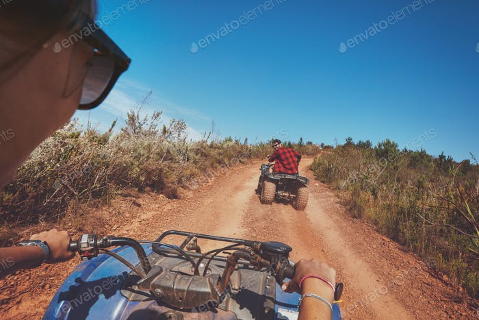 Young people driving quad bikes