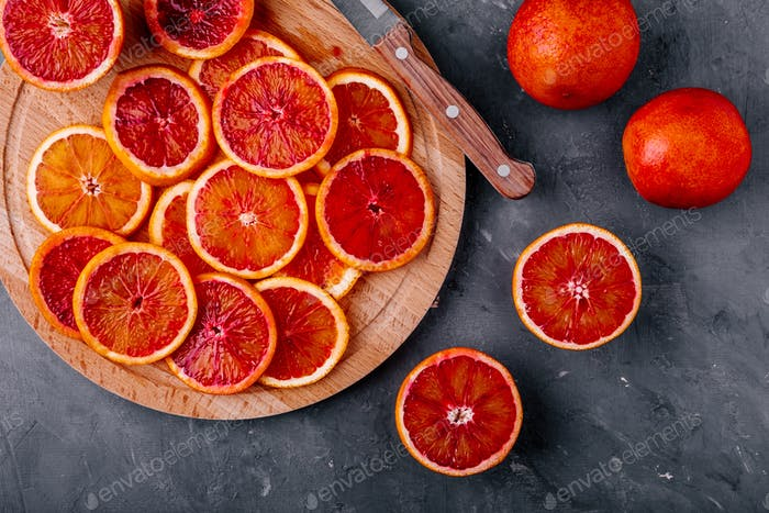 Sliced ripe juicy Sicilian Blood oranges on dark background.