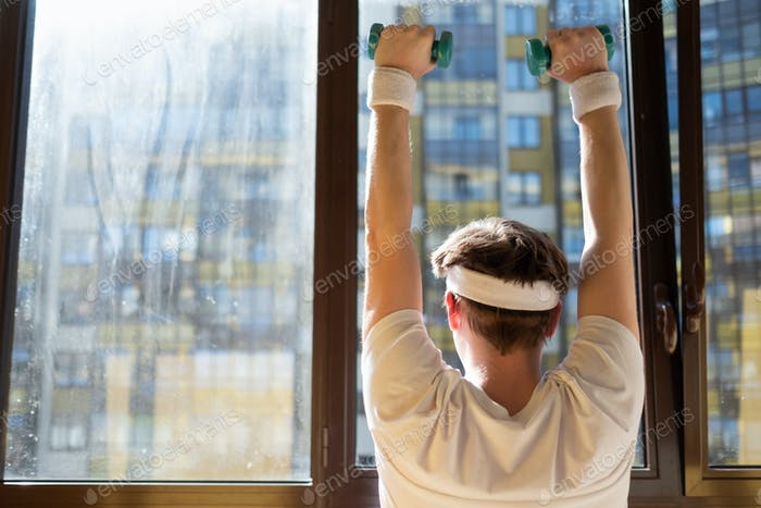 Mature man exercising at home holding weights near window