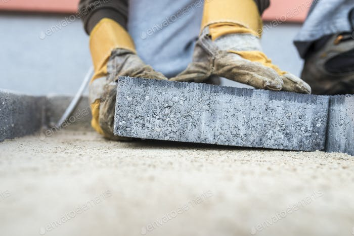 Building contractor laying a paving slab