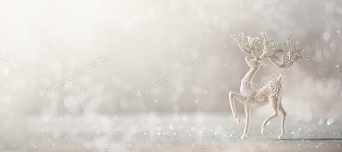 Silver glitter Christmas deer on grey background with lights bokeh, copy space. Greeting card for