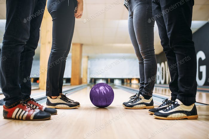 Bowling team, feet in house shoes and ball on lane