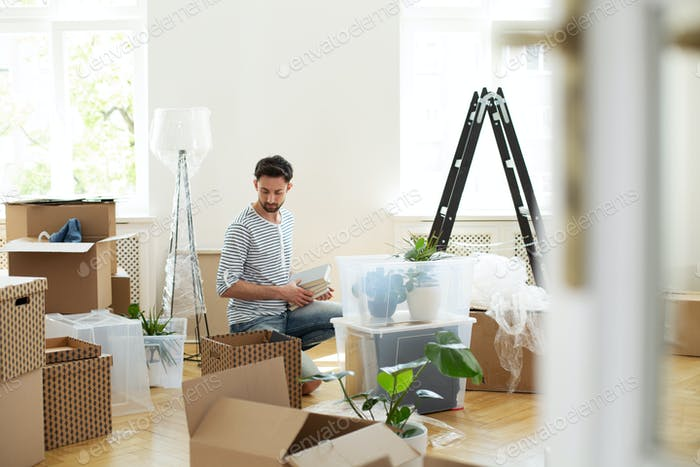 Man unpacking stuff from carton boxes after relocation to new ho