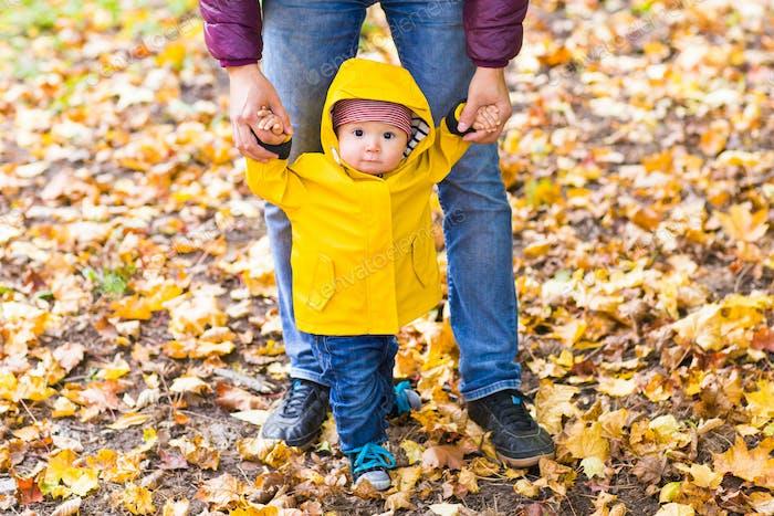 Vater und Sohn gehen. Baby erste Schritte mit Vater Hilfe im Herbst Garten in der Stadt