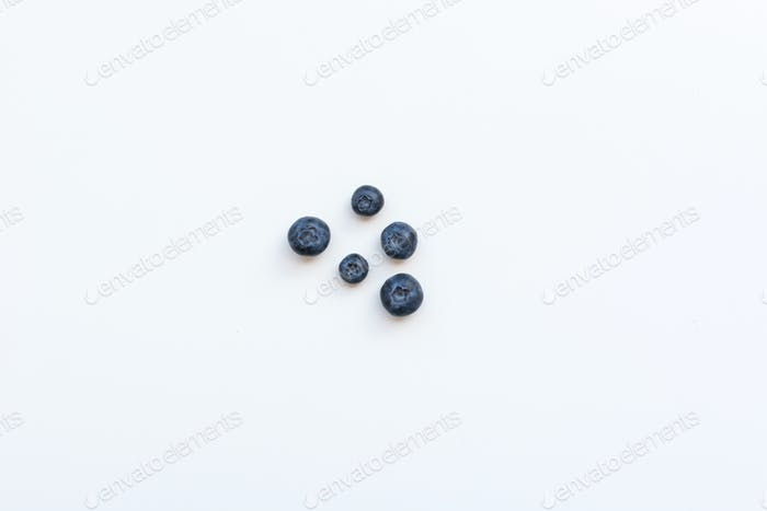 Playful fresh blueberries on a white background