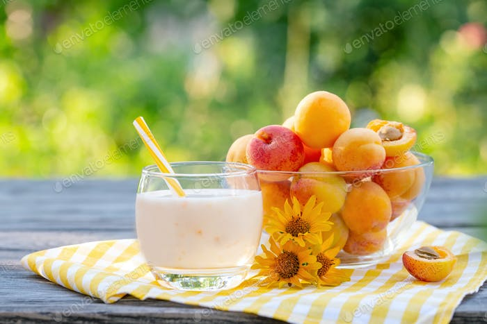 Apricot smoothie or yogurt with apricots on wooden table