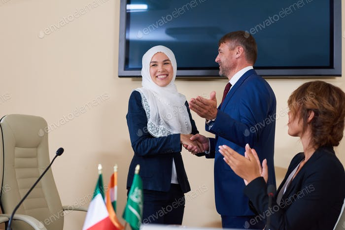 Young confident businessman shaking hand of successful female speaker