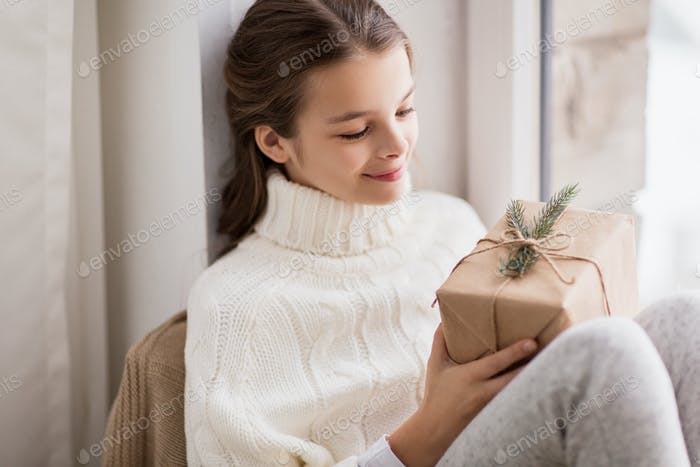 girl with christmas gift sitting at home