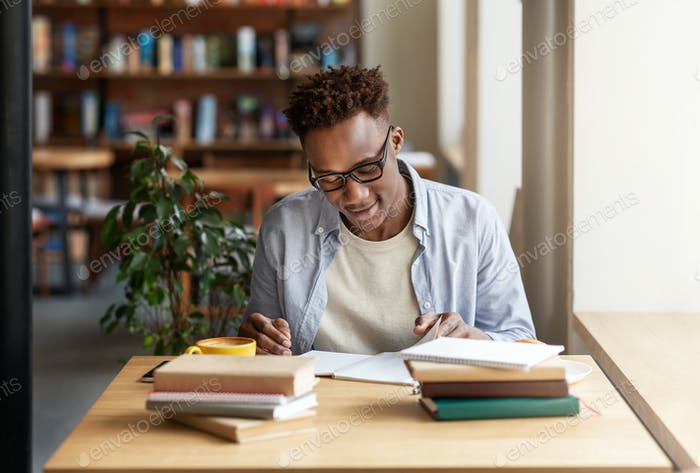 Happy black guy studying or working with books at coffee shop