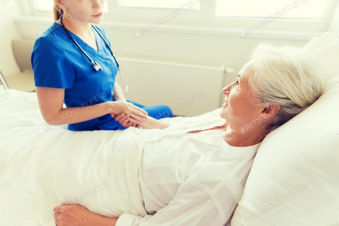 doctor or nurse visiting senior woman at hospital