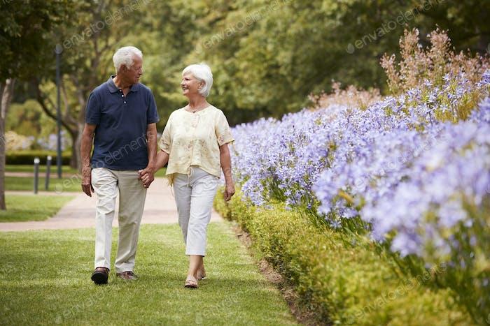 Senior paar halten Hände auf romantische Spaziergang in park zusammen