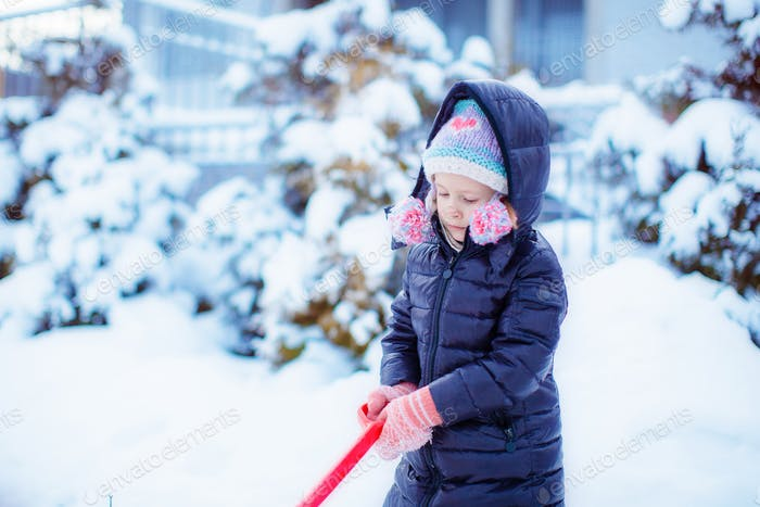 Little adorable girl in snow sunny winter day