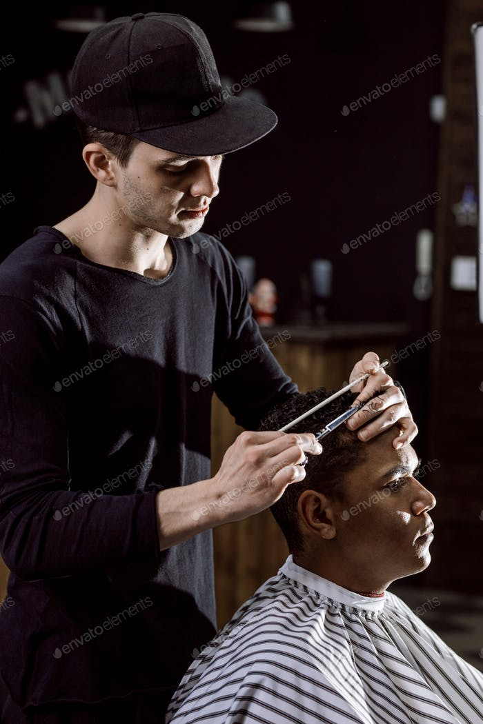 The barber dressed in black clothes is cutting a man's hair holding scissors and comb in his