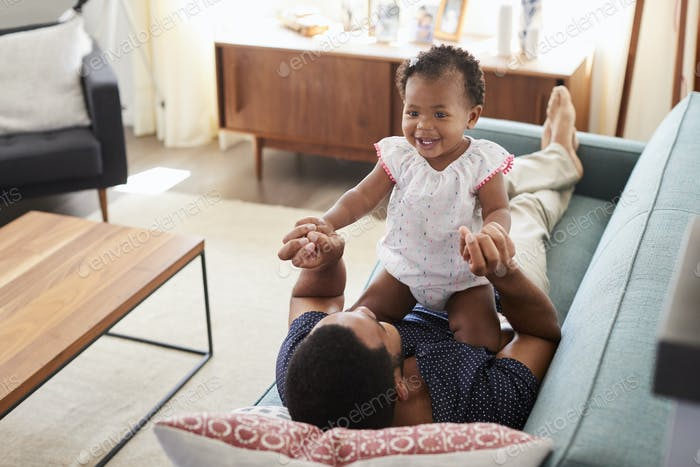 Father Lying On Sofa At Home Playing With Baby Daughter